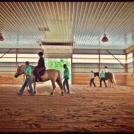 indoor arena with riders
